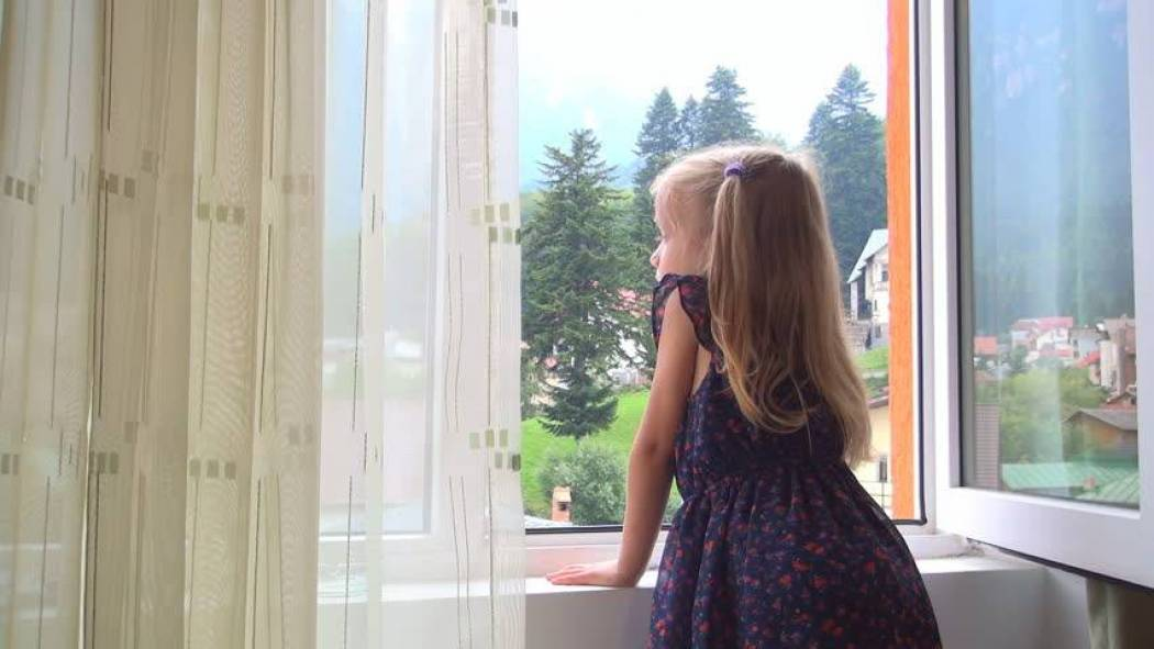 Child looking out from window 3